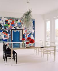 sunny miami townhouse showcases the best of italian midcentury in the spare and elegant white backdrop of the dining room the dynamic geometry of a large scale painting by german artist thomas scheibtz and a