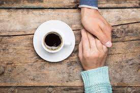 top of coffee cup man holds woman u0027s hand with cup of coffee top view image on wooden