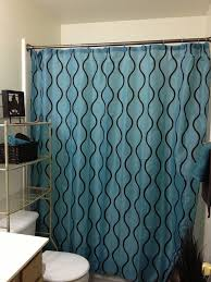 teal and brown shower curtain with racks and sink also towel shelf