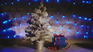 small silver tree with gifts blue garland background