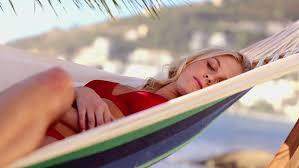 attractive blonde woman sleeping on a hammock on the beach stock