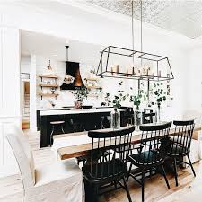 kitchen with long wood dining table and black and white chairs