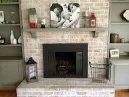 beige brick fireplace with rectangle black metal firebox and grey