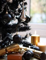 black christmas tree with silver and black balls and gold candles