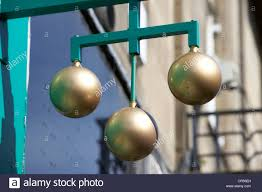 three golden balls pawnbroker symbol outside a pawn shop in the uk