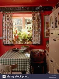 green checked cloth on table beneath window with floral curtains