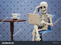 talking halloween skeleton skeleton talking smartphone while working laptop stock photo
