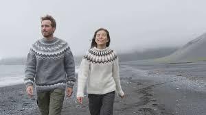 iceland couple wearing icelandic sweaters on sand