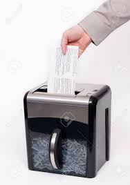 a man putting confidential documents into a paper shredder stock