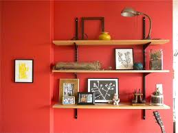 3 brown wooden wall shelves on red wall completed by grey study