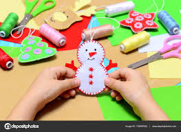 small child holding a felt christmas snowman in hands little kid