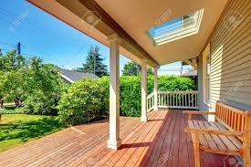 large covered porch with skylight and wood bench and floor with