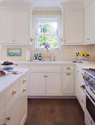 white kitchen cabinets with glass cup pulls polished brass cup pulls with white cabinets cottage kitchen