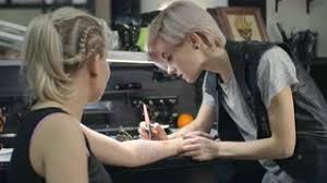 female tattoo artist drawing with felt tip pen on the arm of young