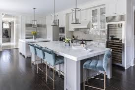 gray kitchen island with blue velvet tufted counter stools