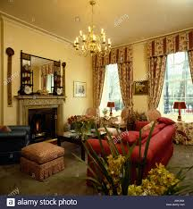 red sofa in neutral livingroom with patterned curtains stock photo