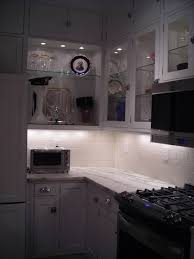 picture of glass front kitchen cabinets with decorative puck lights inside