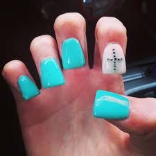 turquoise nails with white accent nail and silver cross with
