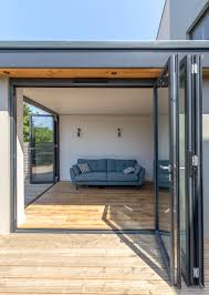 residential extension corner opening flat roof overhang detail modern fold doors grey aluminium profile level threshold timber decking roof ideasmodern byhouse extensionsflat