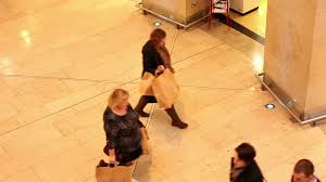 crowd of people walking in shopping mall before christmas looking