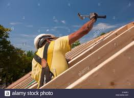hispanic carpenter using a hammer on the roofing at a house under