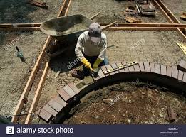 workman leveling bricks to make a step to a backyard patio in