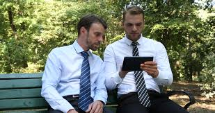 Bench Couple Shirt - business couple with tablet and cellphone in the park dolly shot