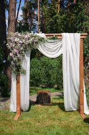 wedding arch log arch for the wedding ceremony of beige cloth and wooden logs in