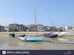 lots of small boats on the beach at low tide in st ives cornwall