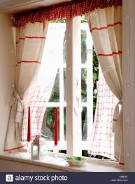 red striped white linen curtains with red checked pelmet at open