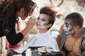 looking for a makeup artist clown looking at woman getting makeup backstage stock photo