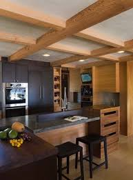 wooden exposed ceiling and kitchen set with black marble top in