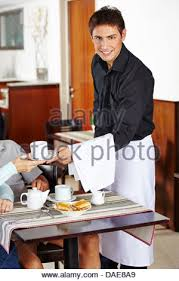 Cleaning Table Stock Images Royalty by Smiling Waiter In Restaurant Cleaning Dining Table Stock Photo