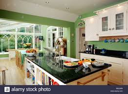 granite topped island unit in large green kitchen with