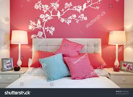 stylish brightly decorated modern bedroom wall stock photo stylish brightly decorated modern bedroom with wall mural and cushions