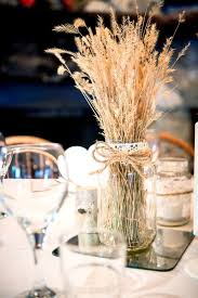 picture of a mason jar centerpiece with lace twine and wheat on a