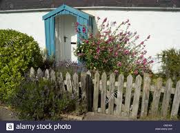 tiny cottage with turquoise painted porch and picket fence stock