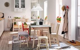 a light dining room with white stained dining table and chairs