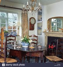 dining table in front of fireplace rush seated ladder back chairs and antique oak table in front of