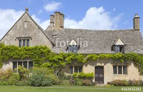 charming old stone house with climbing wisteria on the wall and