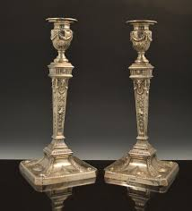 a pair of silver candlesticks in the style of robert adam by