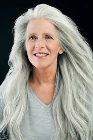 hair colours best for women in their sixties mature woman in her sixties in front of black background having