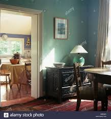 lamp on carved wooden chest beside doorway to kitchen in green lamp on carved wooden chest beside doorway to kitchen in green townhouse dining room with antique