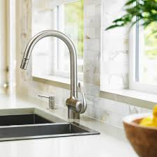how to clean hard water deposits plumbing close up of stainless steel kitchen faucet with marble subway backsplash