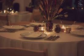 candle lit tables with center pieces and pine cones with mini