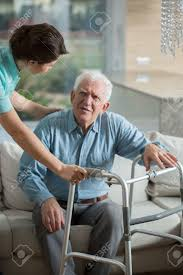 disabled man using walking frame and helpful nurse stock photo