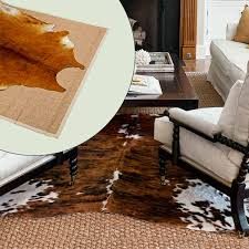 cowhides layered over natural fiber rugs natural fiber rugs cow