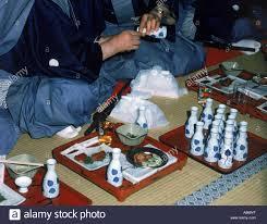 Restaurant Mats Men Sitting On Floor Mats Drinking Small Vases Of Warm Sake In
