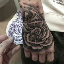 man with hand tattoo of detailed money rose one hundred dollar