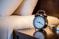 sveglia comodino letto sudicio con la sveglia sul comodino fotografia stock